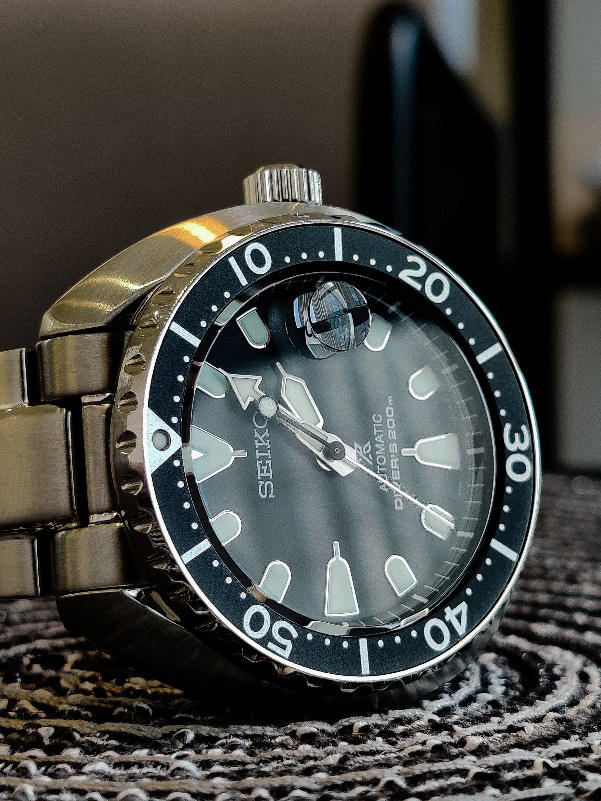 A Seiko SKX007 laying on a table at 02:05